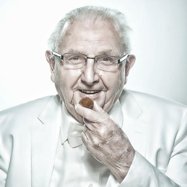 Oudere man in wit pak eet een bitterbal