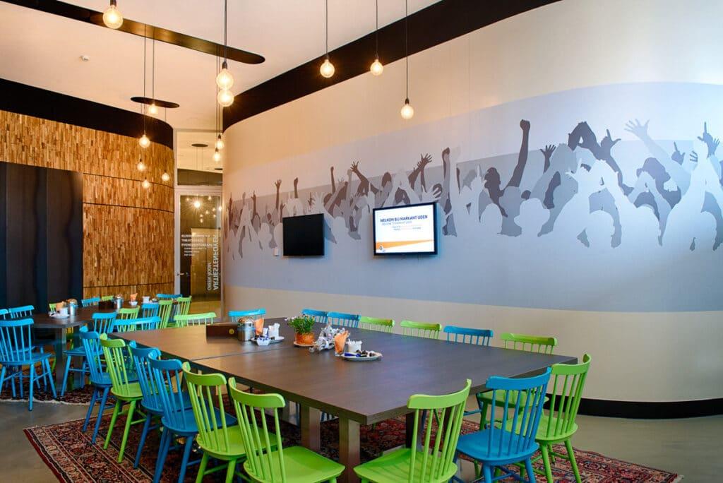Detail opname Theater Markant tafel met kleurrijke stoelen en een afbeelding op de achterwand